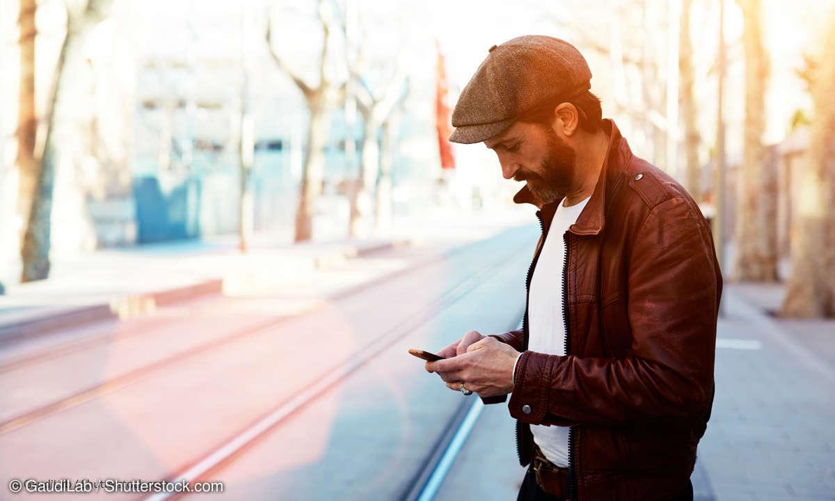 Mann mit Smartphone auf der Straße