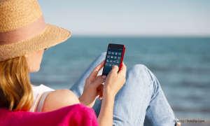 Frau mit Smartphone am Strand