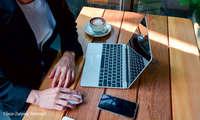 Laptopnutzer mit Smartphone