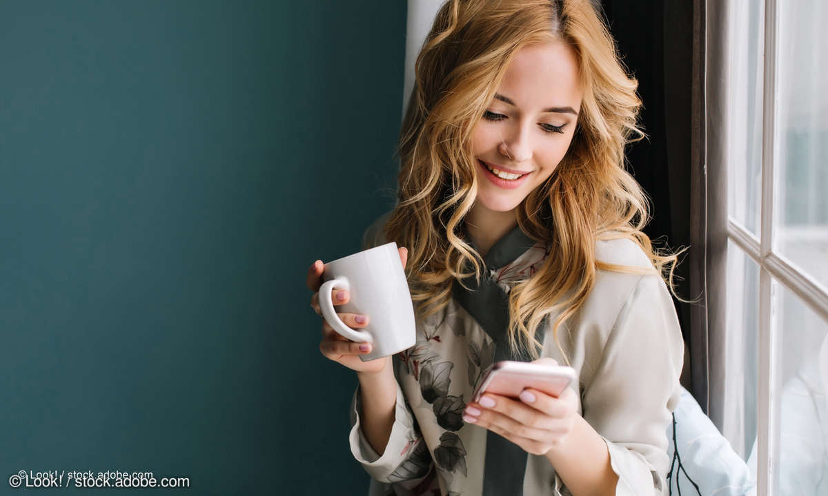 Frau mit Tasse und Smartphone
